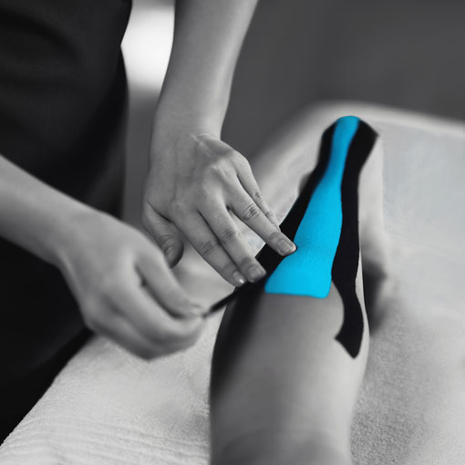 Therapist applying kinesio tape to patients calf.
