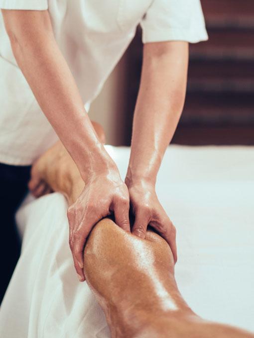 Physical therapist massaging athlete's leg.